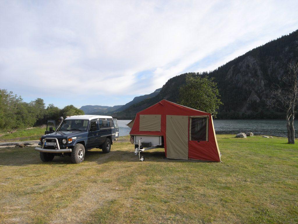 Auto und aufgebauter Zeltanhänger vor dem Fjord