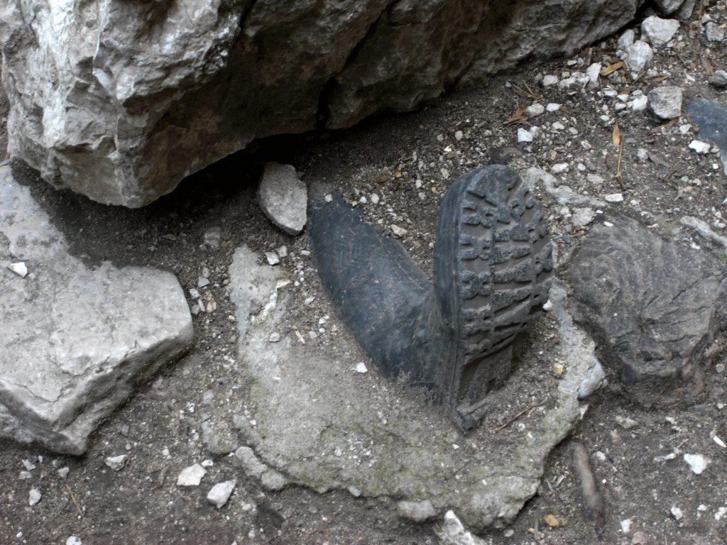 Gummistiefel einbetoniert neben einem Felsblock. Erweckt den Eindruck einer verschütteten Person.
